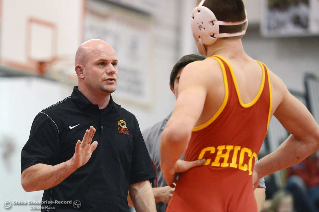 . Chico High\'s coach Keith Rollins (left) talks to Nicholas Maximov (right) who wrestles against Orland High\'s Omar Ortega in the 182 lbs wrestling match at CHS Wednesday, December 18, 2013 in Chico, Calif. (Jason Halley/Chico Enterprise-Record)