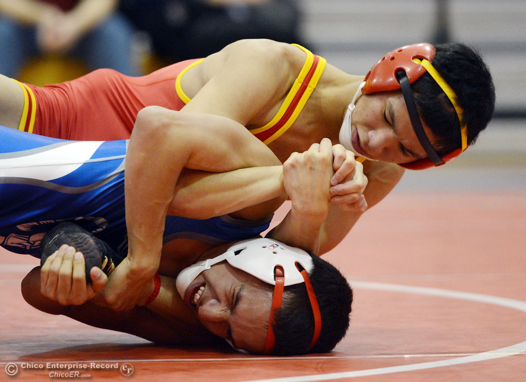 . Chico High\'s Morgan Sauseda (top) wrestles against Orland High\'s Hugo Punzo (bottom) in the 113 lbs wrestling match at CHS Wednesday, December 18, 2013 in Chico, Calif. (Jason Halley/Chico Enterprise-Record)