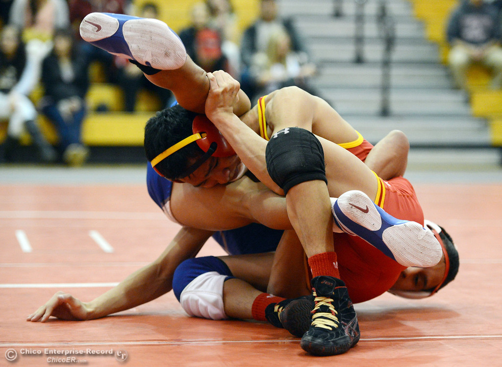 . Chico High\'s Morgan Sauseda (front) wrestles against Orland High\'s Hugo Punzo (back) in the 113 lbs wrestling match at CHS Wednesday, December 18, 2013 in Chico, Calif. (Jason Halley/Chico Enterprise-Record)