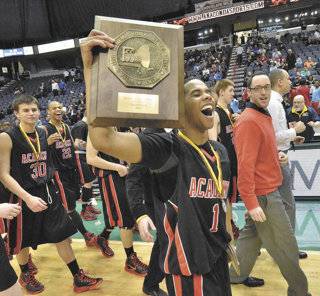 Albany Academy Darrien White, tourney MVP holds up the Federation Trophy after they  beat John Adams high school 50-34 class-A Federation basketball championship at the Times Union Center, Albany.   (Mike McMahon / The Record)