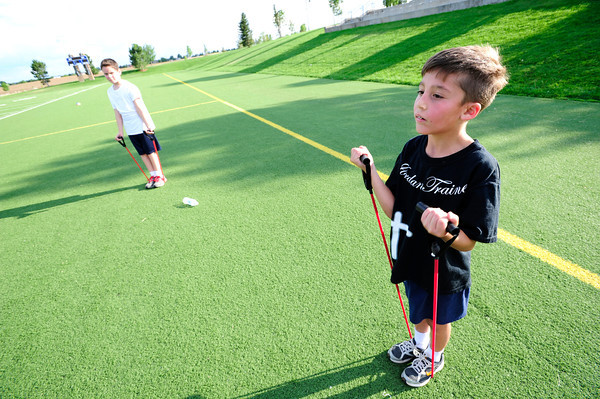 Dillon Roman, right,  lifts against a resistance band with partner Isaac Forbush, right,  during a youth endurance camp at Broomfield County Commons Park on Monday July 9, 2012.<br /> Photo by Paul Aiken