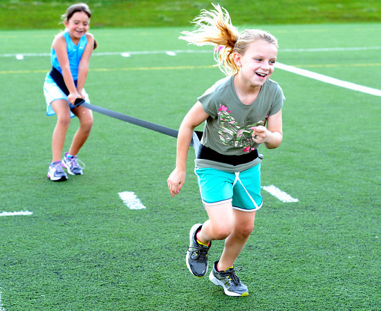 Tori Kilgour, left holds the resistance band as partner Reilly Bayliss does a high step run across the field during a youth endurance camp at Broomfield County Commons Park on Monday July 9, 2012.<br /> Photo by Paul Aiken