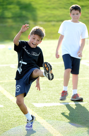 Dillon Roman, left, works on a high leg drill with partner Isaac Forbush during a youth endurance camp at Broomfield County Commons Park on Monday July 9, 2012.<br /> Photo by Paul Aiken