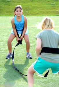 Tori Kilgour, left works on a leg squat drill with partner Reilly Bayliss during a youth endurance camp at Broomfield County Commons Park on Monday July 9, 2012. Photo by Paul Aiken