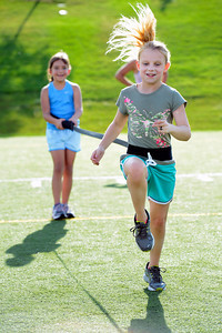 Tori Kilgour, left holds the resistance band as partner Reilly Bayliss does a high step run across the field during a youth endurance camp at Broomfield County Commons Park on Monday July 9, 2012. Photo by Paul Aiken