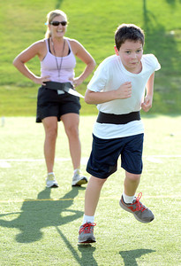Isaac Forbush, runs against a resistance band as instructor Veronica Mueller creates the resistance for the drill during a youth endurance camp at Broomfield County Commons Park on Monday July 9, 2012. Photo by Paul Aiken