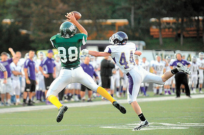 Medina's Troy Grabowski makes a catch over North Royalton's Kevin Gilligan during the first quarter of a game Friday, Sept. 27, 2013. Medina students and players wore yellow, the freshman class color, to show their support for one another after the apparent suicide of a classmate. JUDD SMERGLIA/GAZETTE