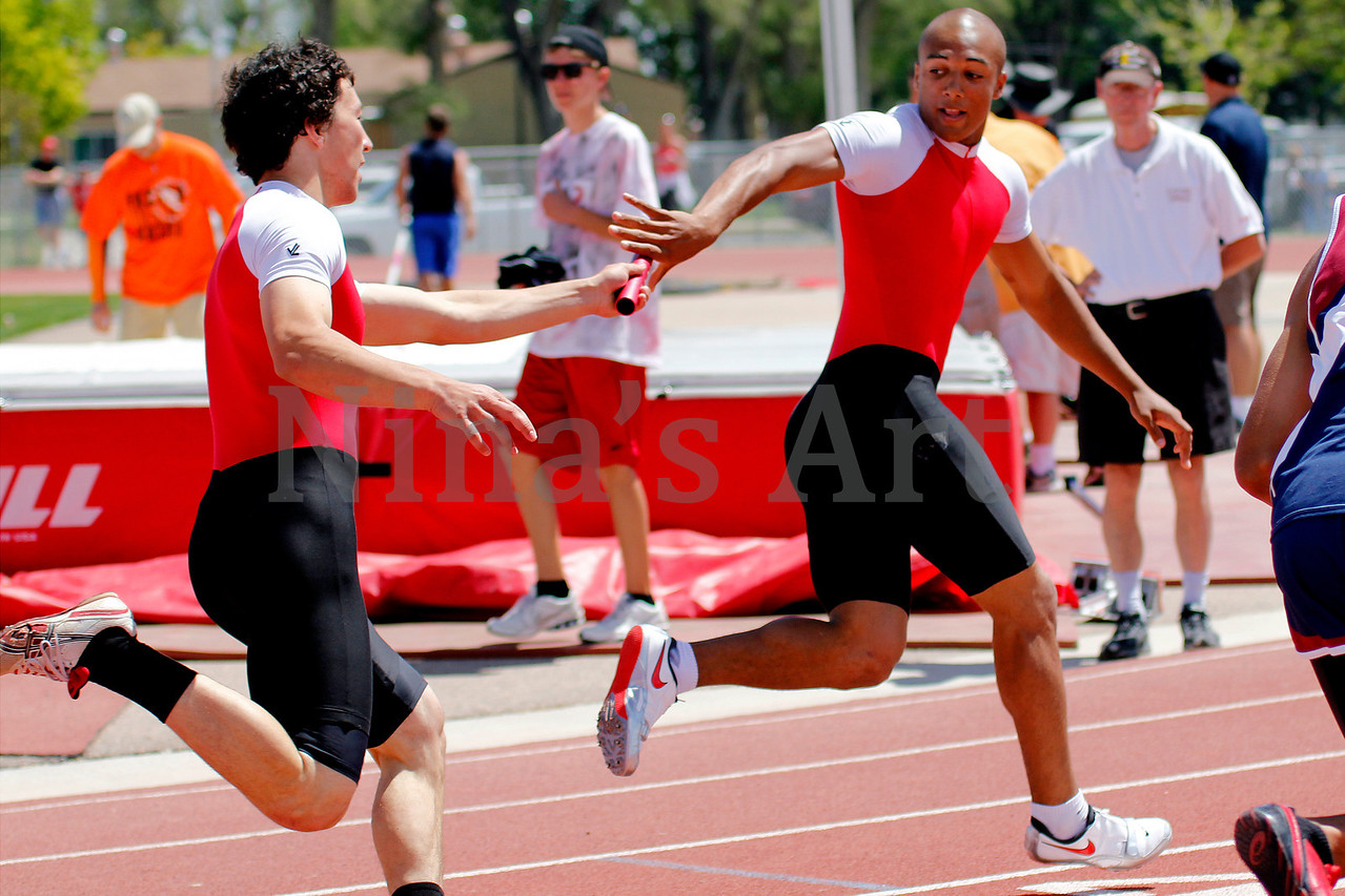 Sean Earley hands the baton off to Austin Ekelerin the 4x100 relay  The Reds just edged out thier competition to win this race