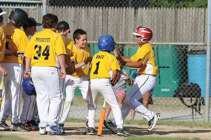 Leominster Nationals' player Nick Garcia gets mobbed by teammates at home plate after his home run hit during their game on Thursday night against North Leominster. SENTINEL & ENTERPRISE/JOHN LOVE