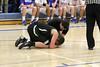 Danville's trainer Dalton Boland kneels next to West Burlington's Springer DeRosear (#33) after a supposed injury on the court.