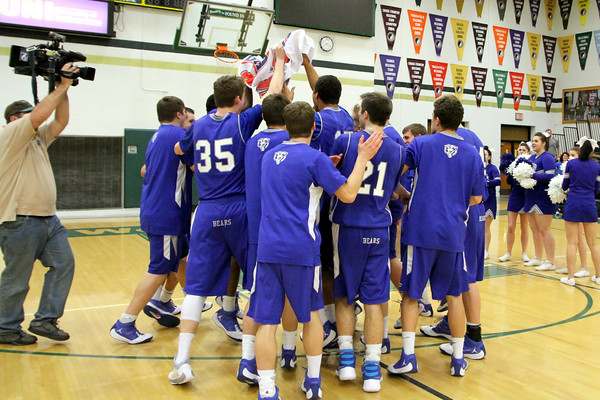 The Danville basketball team clutches to the State Qualifier banner.