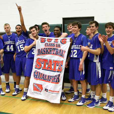 The Danville basketball team cheers while posing with their State Qualifier banner.