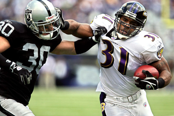 Chris Ammann/Baltimore Examiner Ravens running back Jamal Lewis, right, delivers a stiff arm to the Raiders' Stuart Schweigert during Baltimore's  28-6 win over Oakland at M&T Bank Stadium on Sunday, Sept. 17, 2006. On Sunday, Lewis became the Ravens' all-time combined yardage leader.