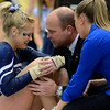 Women's gymnastics coach Jeff Thompson speaks to gymnast Samantha Musto, who injured her knee landing in her floor routine.  The Women's Gymnastics Home Opener was held on January 19, 2013 at Rec Hall, where Penn State competed against Kent State, Minnesota, and Towson.<br /> ©The Daily Collegian