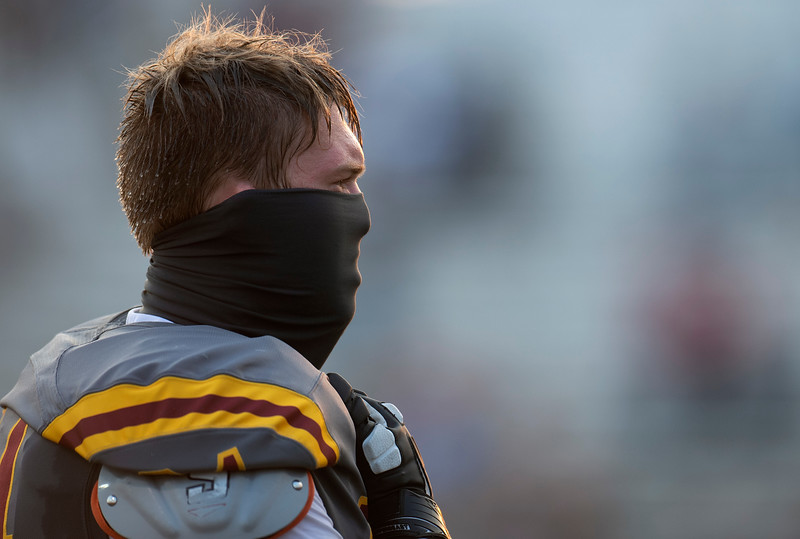 A Rocky Mountain player wears a facial covering as he stands during the national anthem before the first high school football game of the season at French Field at Rocky Mountain High School in Fort Collins, Colo. on Thursday, Oct. 9, 2020.