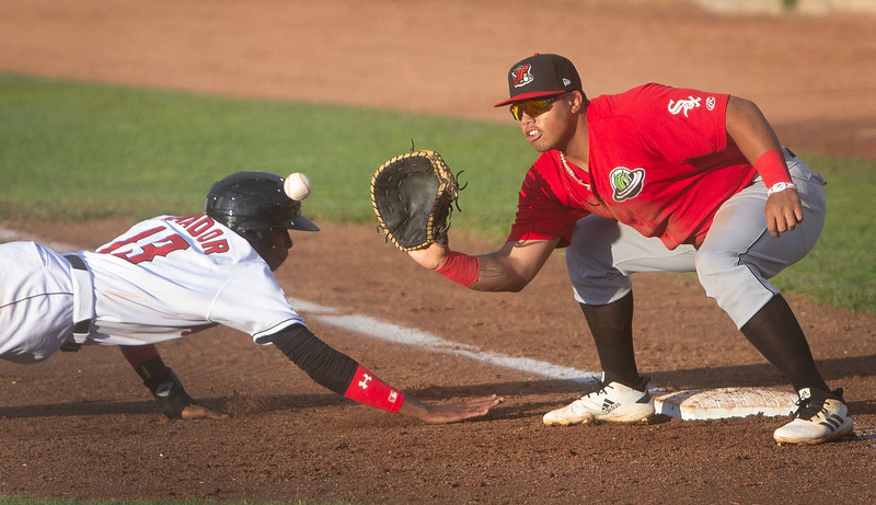 Mustangs' Ranser Amador (13) slides back to first base as Voyagers' Harvin Mendoza (17) looks to catch the ball in the fourth inning of the game at Dehler Park in Billings, Mont. on Wednesday, June 19, 2019.