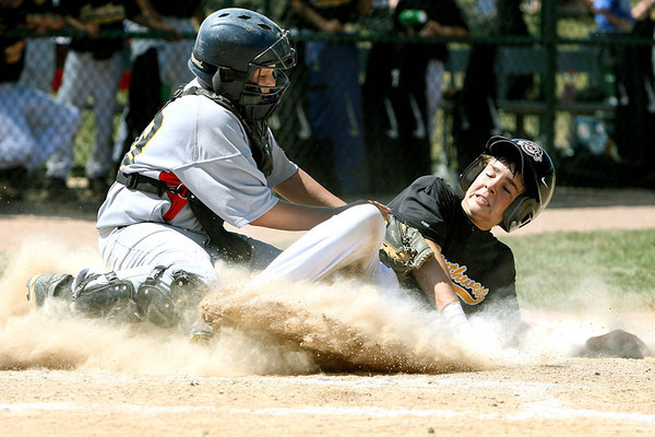 Chris Ammann/Baltimore Examiner Dylan Cross, of Bryant, Arkansas, slides safely into home on a delayed steal, ahead of the tag of Josh Tayman of St. Mary's County during the Cal Ripken World Series in Aberdeen on Thursday, August 17, 2006.