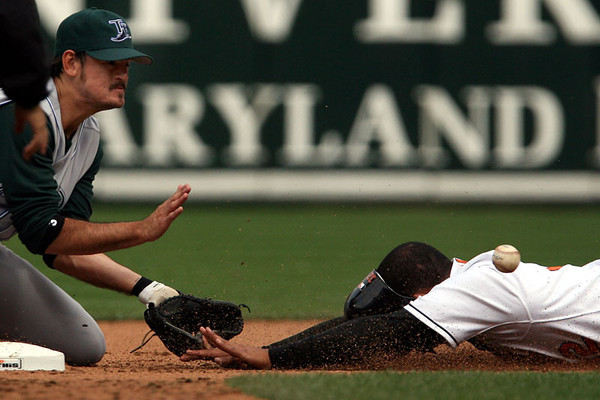Chris Ammann/Examiner Baltimore Orioles outfielder Luis Matos, right, has his helmet slide off while diving into second base during Opening Day at Oriole Park at Camden Yards on Monday, April 3, 2006 in Baltimore.