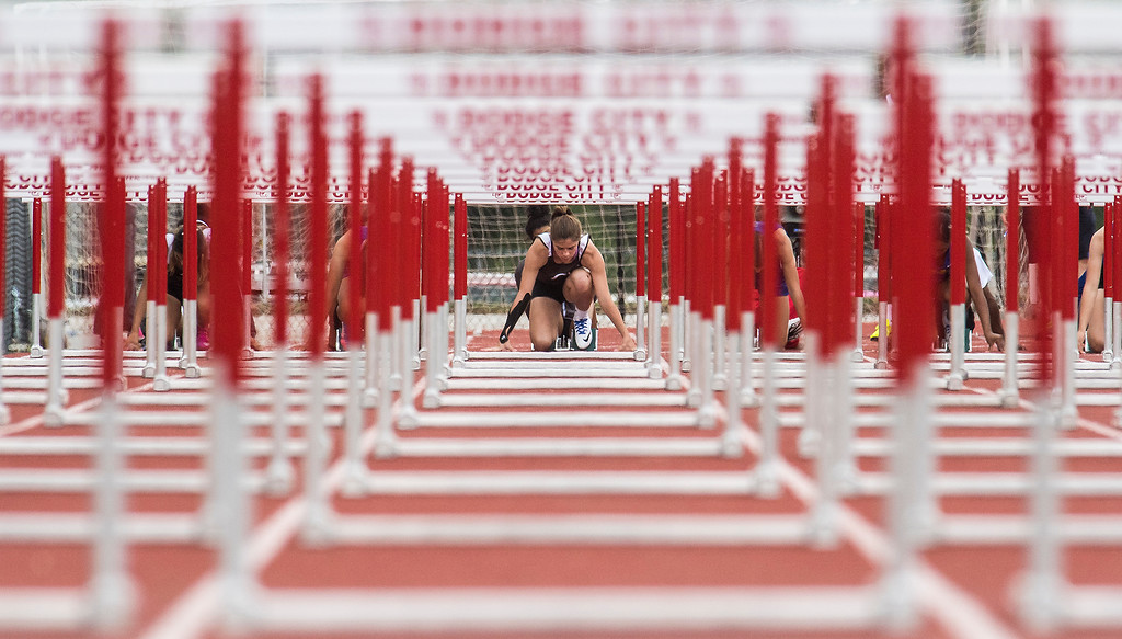 Garden City High School junior Annie Gerber sets up on the blocks for competition in the women's 100 meter hurdles finals during the Class 6A regional track and field meet in Dodge City Thursday. Gerber placed fourth to secure a spot at the state championship next weekend.