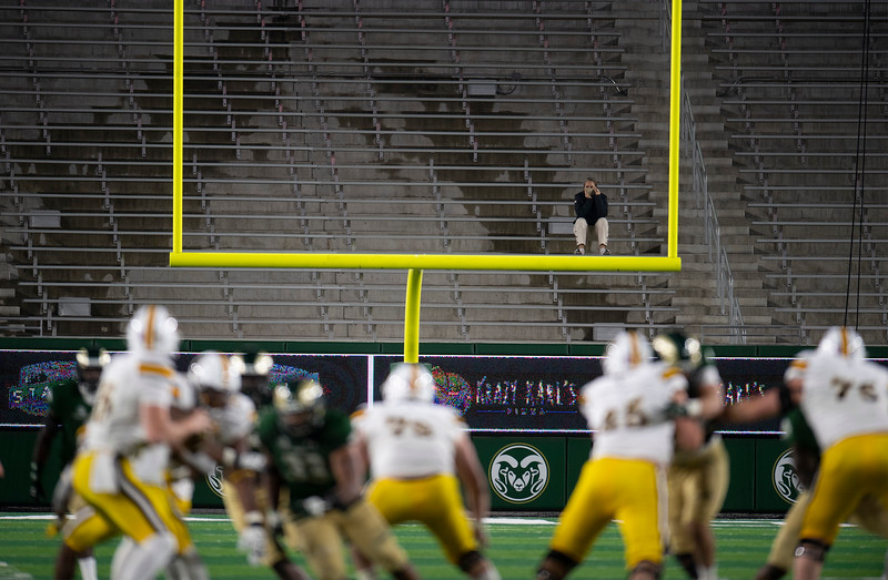 A woman sits alone in the stands during the fourth quarter of the game between the Wyoming Cowboys and the Colorado State Rams at Colorado State University in Fort Collins, Colo. on Thursday, Nov. 5, 2020.