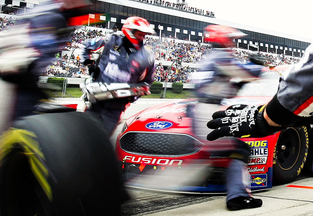 Greg Biffle, driver of the #16 Ford Ecoboost Ford Fusion, pits as the pit crew changes tires during the NASCAR Sprint Cup Series Pennsylvania 400 at Pocono Raceway on August 1, 2016 in Long Pond, Pennsylvania.