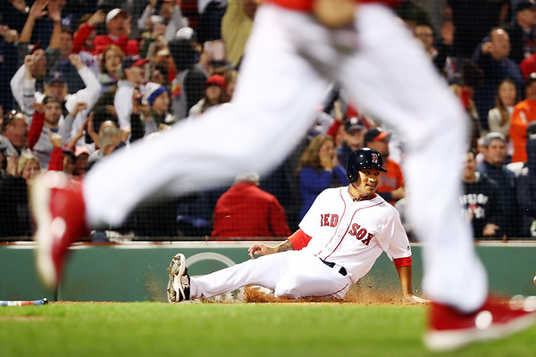 Tzu-Wei Lin #30 of the Boston Red Sox slides into home plate to score the game-winning run as his teammates rush the field after Mitch Moreland #18 of the Boston Red Sox hits the game-ending walk off in the ninth inning during a game against the Houston Astros at Fenway Park on September 9, 2018 in Boston, Massachusetts.
