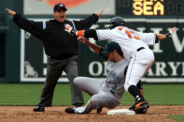 Chris Ammann/Examiner Baltimore Orioles first baseman Kevin Millar, right, helps umpire Mark Wegner make the call as Millar safely alludes Jorge Cantu's tag during Opening Day at Oriole Park at Camden Yards on Monday, April 3, 2006 in Baltimore.