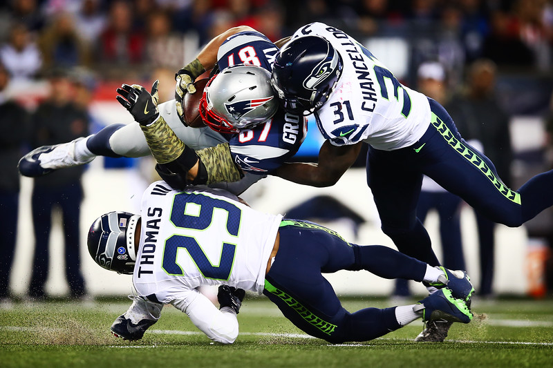 Rob Gronkowski #87 of the New England Patriots is tackled after making a catch by Earl Thomas #29 and Kam Chancellor #31 of the Seattle Seahawks during the second quarter of a game at Gillette Stadium on November 13, 2016 in Foxboro, Massachusetts.