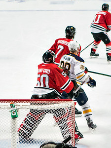 Corey Crawford moving Jamie McGinn out of his crease.