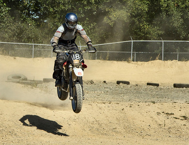 # 18 - Adrian Hein going over a jump in the dirt section at the BC Supermoto season wrapup race day, Sept 4th, 2011