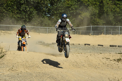 # 18 - Adran and # 117 - Don McLennan ride the jumps in the dirt section