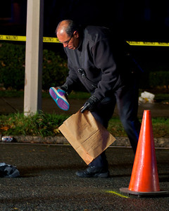 110812, Somerville, MA - A police officer collects a shoe that was left behind in the middle of Powder House Boulevard near its intersection with Packard Avenue after a pedestrian was struck by a vehicle. Herald photo by Ryan Hutton