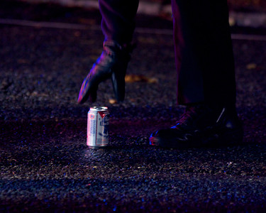 110812, Somerville, MA - A police officer collects a beer can that was left behind in the middle of Powder House Boulevard near its intersection with Packard Avenue after a pedestrian was struck by a vehicle. Herald photo by Ryan Hutton