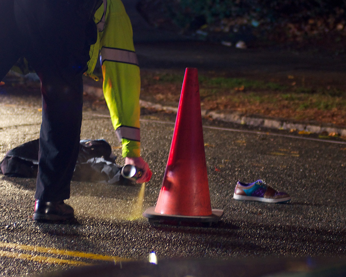 110812, Somerville, MA - A police officer marks part of Powder House Boulevard near its intersection with Packard Avenue after a pedestrian was struck by a vehicle. In the road is a shoe and other items of clothing. Herald photo by Ryan Hutton