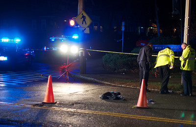 110812, Somerville, MA - Police survey Powder House Boulevard near its intersection with Packard Avenue after a pedestrian was struck by a vehicle. In the road is a shoe and other items of clothing. Herald photo by Ryan Hutton