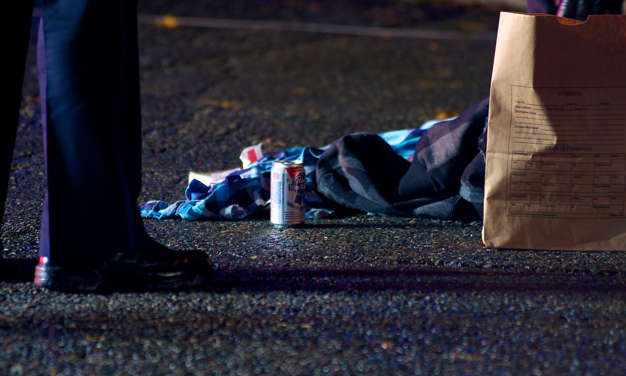 110812, Somerville, MA - A beer can, a book and articles of clothing litter Powder House Boulevard near its intersection with Packard Avenue after a pedestrian was struck by a vehicle. Herald photo by Ryan Hutton