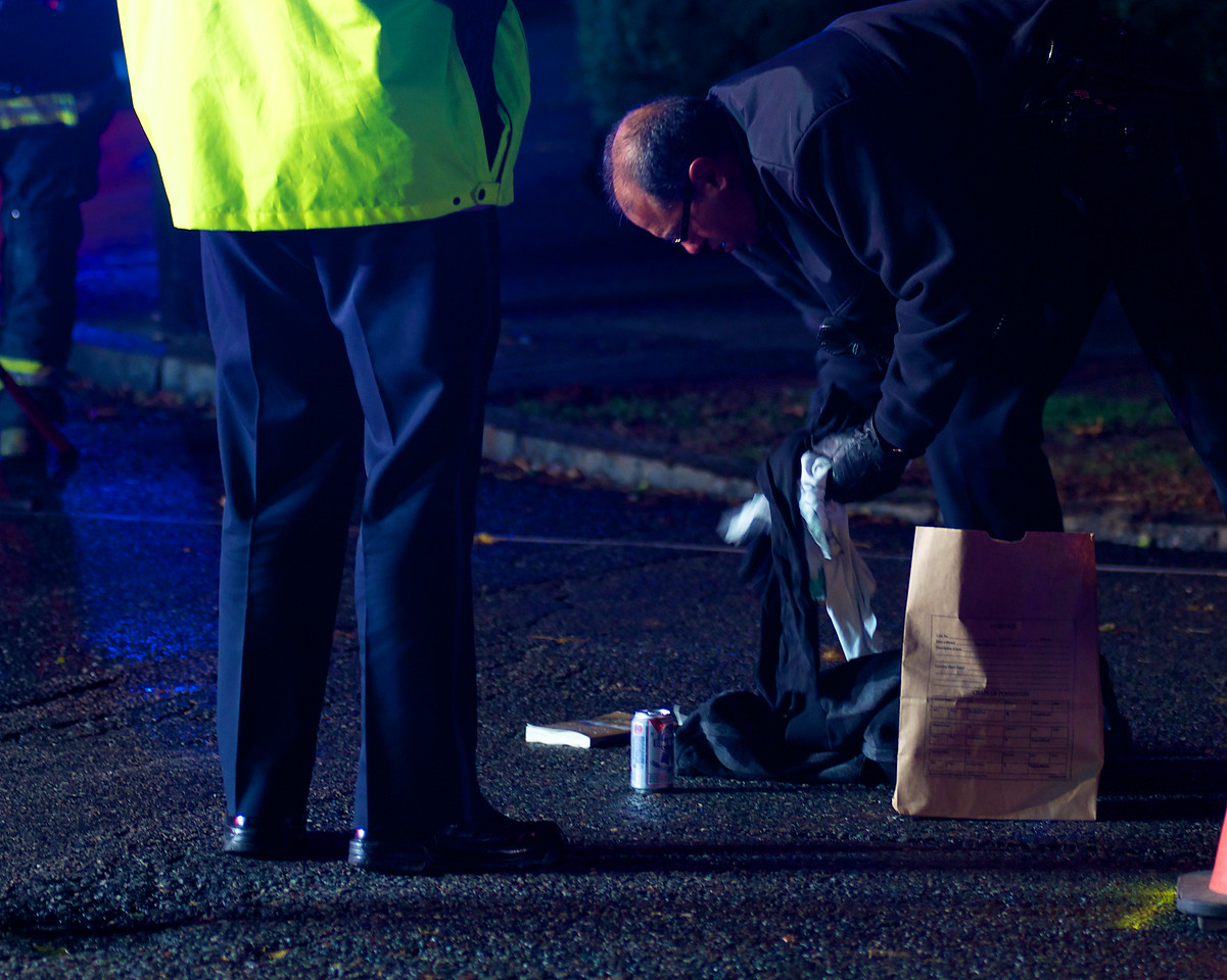 110812, Somerville, MA - A police officer collects clothing that was left behind in the middle of Powder House Boulevard near its intersection with Packard Avenue after a pedestrian was struck by a vehicle. The items included a sweatshirt, a pair of shoes, a book and at least one beer can. Herald photo by Ryan Hutton