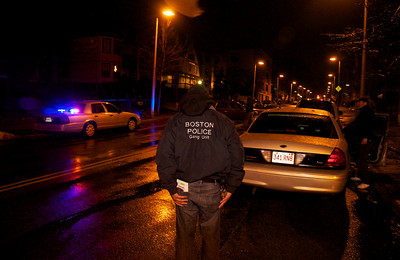 011113, Roxbury, MA - A member of the Boston Police Gang Unit canvases the intersection of Humboldt Avenue and Homestead Street after the shooting of a youth in the area. Herald photo by Ryan Hutton