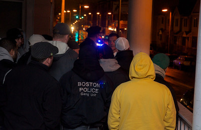 011113, Roxbury, MA - Boston Police officers gather under a porch to stay out of the rain while dividing up canvassing duties after the shooting of a youth at the intersection of Humboldt Avenue and Homestead Street. Herald photo by Ryan Hutton