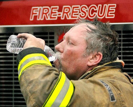 Anderson firefighter Jeff Freeman takes a break and gets some water during the fire at Captain D's Seafood restaurant Monday.