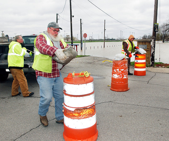 Elwood street department workers put out barricades with sandbags on them to block North 19th Street.