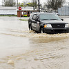 Elwood police drive thru high water on North C Street as they patrol the flooded areas of the city Friday.