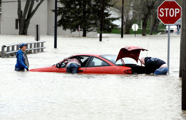 Andy Anderson, middle, unlocks the stirring wheel of his car as he and friends work to get the vehicle out of the deep water at North F Street and North Anderson Street Friday morning after heavy rains flooded the area.