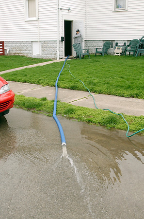 After heavy rains caused flooded streets and basements all around the Elwood area.  Here this member of the Elwood Mission Chapel watches as water is pumped out of their basement Friday.