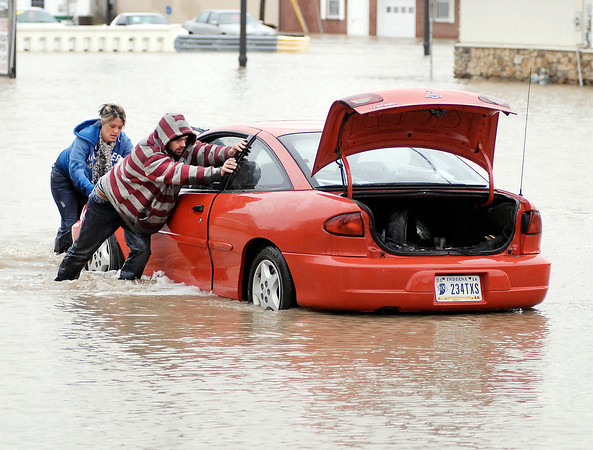 With the help of friends, Andy Anderson pushes his car out of deep water at North F Street and North Anderson Street in Elwood Friday morning after driving into the high water earlier in the morning and stalling out.