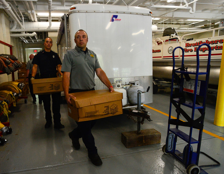 KRISTOPHER RADDER - BRATTLEBORO REFORMER<br /> Brattleboro Firefighter Matt Casabona and Will Streeter move boxes of chicken wings at Central Station as they load of a vehicle with the donated food on June 12, 2018. A truck dropped off nearly 11,000 pounds of chicken wings after a local company turned away the order for a damaged pallet. Armed with phones, the firefighters contacted several local organizations and food banks to help move nearly all of the 289 cases of chicken wings.