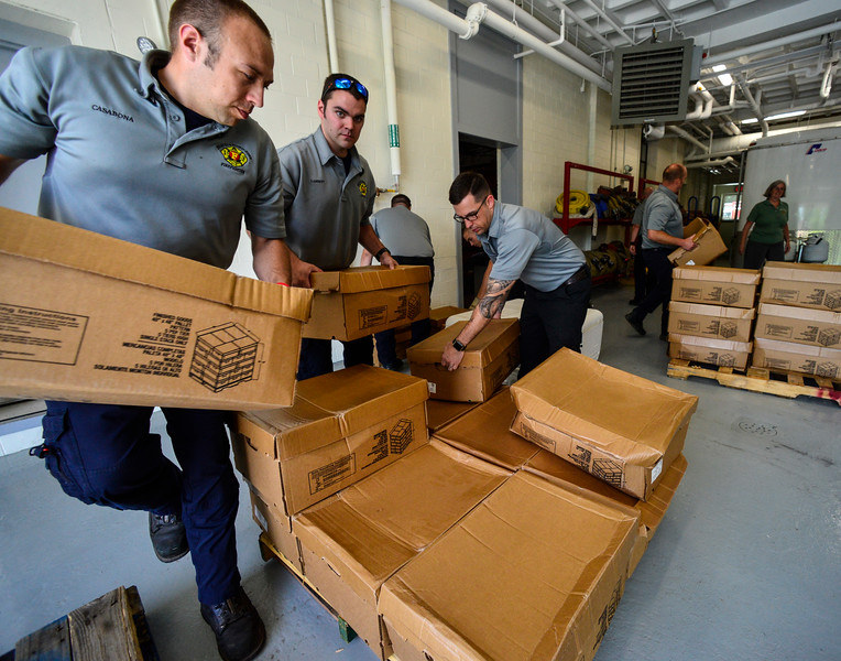 KRISTOPHER RADDER - BRATTLEBORO REFORMER<br /> A group of Brattleboro firefighter loads up a pallet of chicken wings for the Vermont Food Bank at Central Station on June 12, 2018. A truck dropped off nearly 11,000 pounds of chicken wings after a local company turned away the order for a damaged pallet. Armed with phones, the firefighters contacted several local organizations and food banks to help move nearly all of the 289 cases of chicken wings.