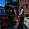 KRISTOPHER RADDER - BRATTLEBORO REFORMER<br /> Brattleboro Firefighters Alex Morin and Eric Poulin help load a car with boxes of chicken wings on Tuesday, June 12, 2018. A truck dropped off nearly 11,000 pounds of chicken wings after a local company turned away the order for a damaged pallet. Armed with phones, the firefighters contacted several local organizations and food banks to help move nearly all of the 289 cases of chicken wings.