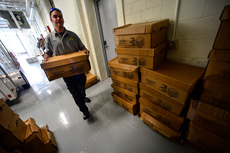 KRISTOPHER RADDER - BRATTLEBORO REFORMER<br /> Brattleboro Firefighter Kevin Lambert helps load up a car with boxes of chicken wings on Tuesday, June 12, 2018. A truck dropped off nearly 11,000 pounds of chicken wings after a local company turned away the order for a damaged pallet. Armed with phones, the firefighters contacted several local organizations and food banks to help move nearly all of the 289 cases of chicken wings.