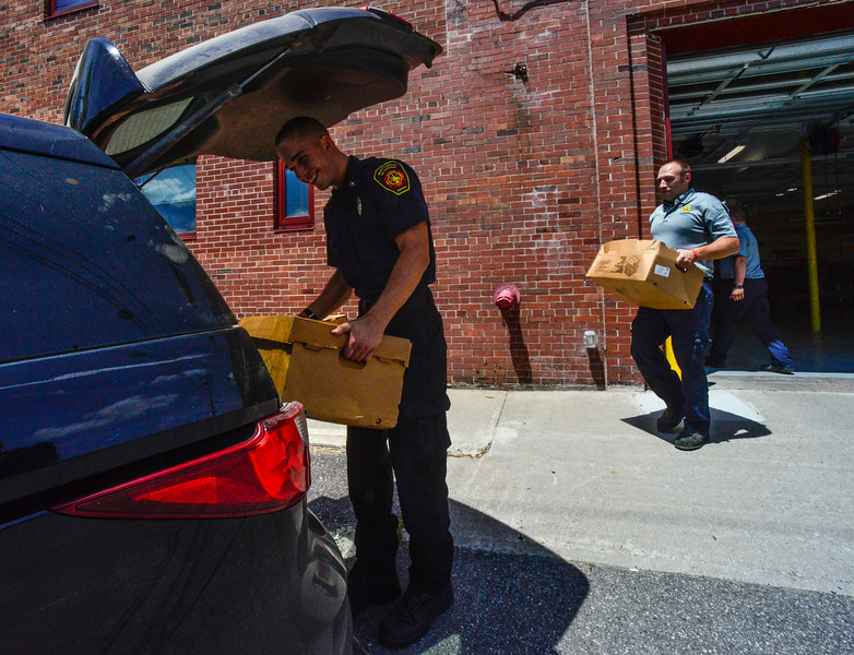 KRISTOPHER RADDER - BRATTLEBORO REFORMER<br /> Brattleboro Firefighter Will Streeter helps load up a car with boxes of chicken wings on Tuesday, June 12, 2018. A truck dropped off nearly 11,000 pounds of chicken wings after a local company turned away the order for a damaged pallet. Armed with phones, the firefighters contacted several local organizations and food banks to help move nearly all of the 289 cases of chicken wings.